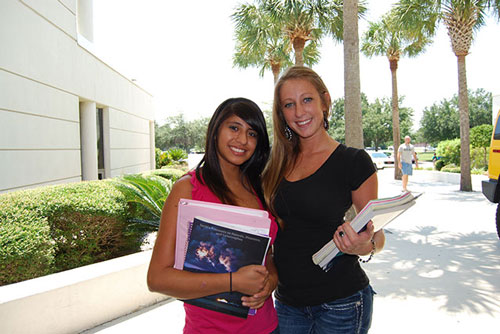 Two female student holding books.