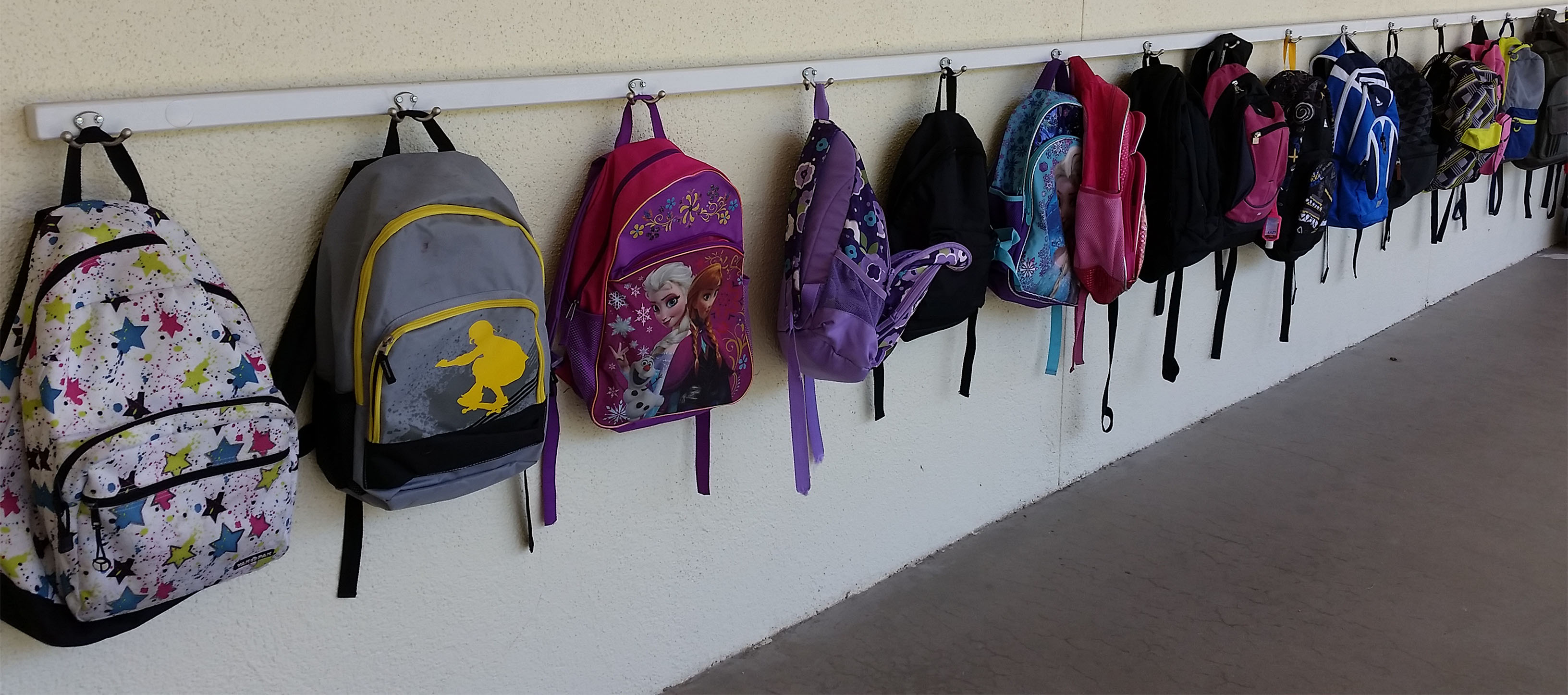 Children's backpacks are neatly hung up at school